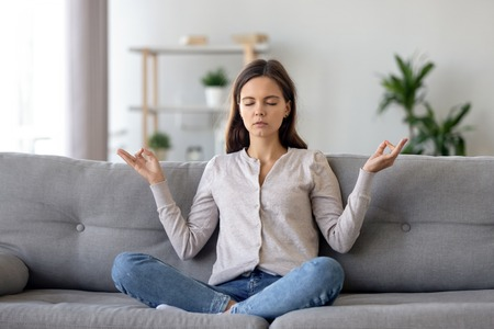 Foto per Peaceful young woman sitting in lotus pose on sofa in living room, meditating, attractive girl with closed eyes practicing yoga at home, stress relief concept, healthy good habit - Immagine Royalty Free
