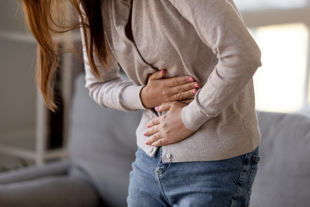 Photo pour Close up woman holding belly, feeling discomfort, health problem concept, unhappy girl standing at home, suffering from stomachache, food poisoning, gastritis, abdominal pain, menstrual period - image libre de droit