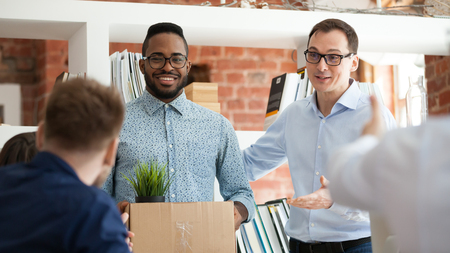 Foto de Black man having first working day getting acquainted with colleagues standing in office in front of workmates. Boss introducing employee, newcomer holds box with belongings starting career in company - Imagen libre de derechos