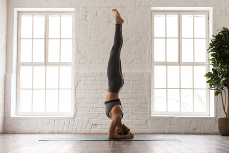 Foto de Young attractive woman practicing yoga, standing in headstand pose, salamba sirsasana exercise, beautiful girl in grey sportswear, leggings and bra working out at home or in yoga studio - Imagen libre de derechos