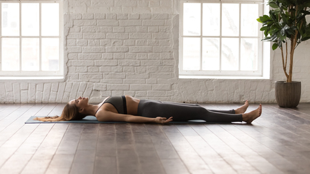 Foto de Calm woman in grey sportswear, pants and bra practicing yoga, lying in Savasana, Dead Body pose on mat, beautiful girl resting after working out at home or in yoga center with white walls - Imagen libre de derechos