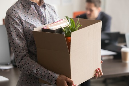 Foto de Close up view of new female employee intern holding cardboard box with belongings start finish job in company office, busnesswoman newcomer worker get hired fired on first last day at work concept - Imagen libre de derechos