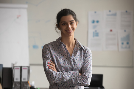Foto de Young indian professional business woman looking at camera in office, confident businesswoman coach, female corporate marketing manager, happy millennial hindu employee smiling posing for portrait - Imagen libre de derechos