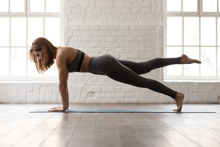 Foto de Sporty woman in grey sportswear, bra and leggings practicing yoga, doing Push ups or press ups exercise, phalankasana, variation of Plank pose, beautiful girl working out at home or in yoga studio - Imagen libre de derechos