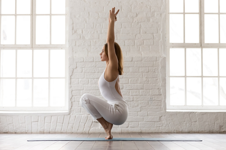 Photo pour Concentrated sporty woman in white sportswear, pants and top standing in Utkatasana pose, Squat, Chair exercise, attractive girl training in modern yoga studio or at home - image libre de droit