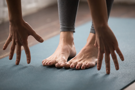 Foto de Young woman practicing yoga, standing in uttanasana pose on mat, doing Head to knees exercise, beautiful girl working out at home or in yoga studio, female hands and feet in grey leggings close up - Imagen libre de derechos