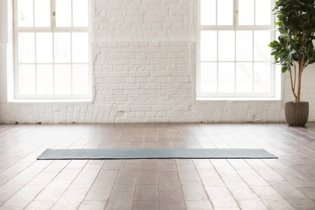 Foto de Yoga mat on natural wooden floor in empty room in fitness center, comfortable space for doing sport exercises, big windows and white brick walls, modern yoga class room with nobody - Imagen libre de derechos