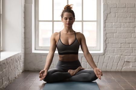 Photo pour Calm woman with closed eyes practicing yoga, sitting in Padmasana pose on mat, Lotus exercise, attractive sporty girl in grey sportswear, leggings and bra working out at home or in yoga studio - image libre de droit