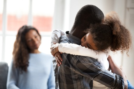 Photo pour Cute little preschool African American daughter hug young father showing love and care, smiling small child girl embrace black father happy to spend time with parents at home. Family wellbeing concept - image libre de droit
