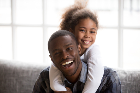 Foto de Headshot of smiling little African American girl piggyback young happy dad relaxing on couch together, portrait of excited black father embrace hug with small kid, posing for family picture at home - Imagen libre de derechos