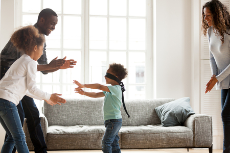 Photo for Funny little blindfolded boy play hide and seek game with mixed race family in living room, toddler have fun with black parents and sister, spend time together laughing entertaining at home - Royalty Free Image