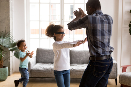 Photo for Smiling little mixed race blindfolded girl have fun with African American dad and toddler brother at home, happy black family play hide and seek laughing and spending time on weekend together - Royalty Free Image