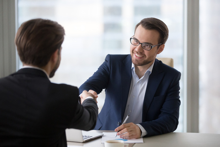 Photo pour Smiling hr manager advisor insurer bank executive handshaking client applicant at meeting or job interview, satisfied businessmen shake hands thanking for good financial business deal, hiring concept - image libre de droit