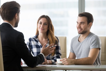 Foto de Couple customers consulting lawyer or about buying house or insurance services, salesman, bank worker or financial advisor making presentation offer to clients at meeting in office - Imagen libre de derechos
