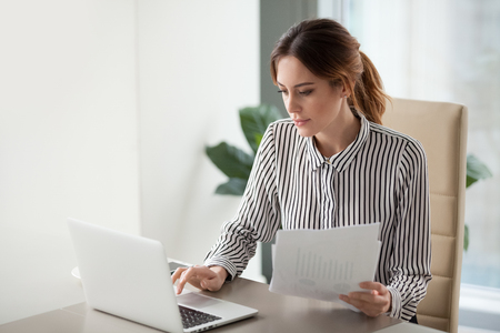 Foto de Serious focused businesswoman typing on laptop holding papers preparing report analyzing work results, female executive doing paperwork at workplace using computer online software for data analysis - Imagen libre de derechos