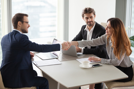 Photo for Businessman handshaking businesswoman making deal finishing group negotiations, satisfied smiling business partners conclude contract agreement shake hands expressing respect thank for group meeting - Royalty Free Image