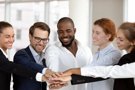 Photo for Six multinational millennial happy employees put join hands together in stack pile at group meeting, success celebration, corporate unity, help support promises in teamwork and team building concept - Royalty Free Image