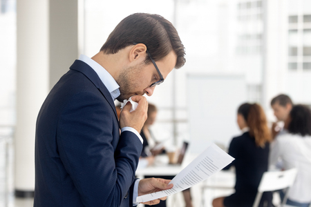 Foto de Side view insecure male holding paper reading preparing for performance feel afraid of public speaking, company staff sitting at desk in background. Fear of job interview fail, stress at work concept - Imagen libre de derechos