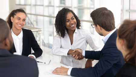 Foto de Multiracial businessman businesswoman shake hands starting collaboration at group negotiations, positive people gathered at modern office boardroom, partnership teamwork and business etiquette concept - Imagen libre de derechos