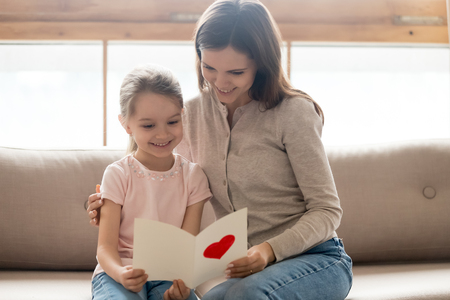 Photo for Happy family young mom and little cute kid daughter holding reading greeting card with red heart sitting on sofa at home, child girl congratulating mum with birthday mothers day making gift present - Royalty Free Image