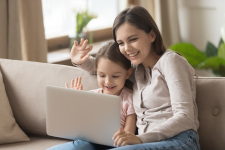 Foto de Happy family young mom with kid daughter looking at laptop screen waving hands make distance video call, smiling mother and little child girl talking to webcamera on internet chat by computer webcam - Imagen libre de derechos