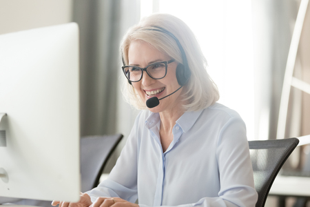 Foto de Happy old businesswoman in headset speaking by conference call looking at computer, mature female aged call center agent operator telemarketer talking consulting customer service support in office - Imagen libre de derechos