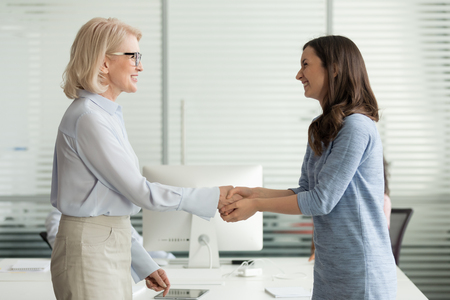 Photo for Happy young girl intern student worker get appreciated promoted hired rewarded handshaking helpful female old boss teacher, businesswomen handshake in office as gratitude recognition thanks concept - Royalty Free Image