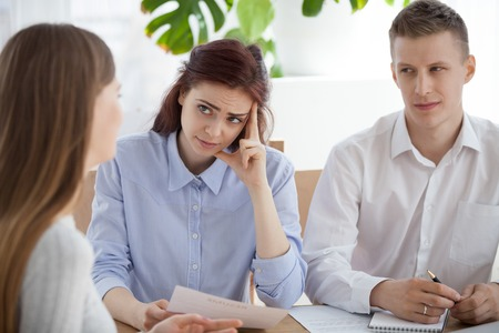 Photo for Serious HR managers advisors interviewing young woman student in the office. Employers holding curriculum vitae and looking at applicant girl with disbelief dissatisfied, bad first impression concept - Royalty Free Image