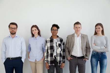 Photo pour Young confident positive multiracial company staff professionals standing together opposite wall looking at camera. Diverse group business people employees posing in the office successful team concept - image libre de droit