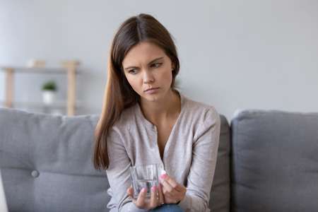 Foto de Lonely sad young woman sitting on sofa at home holding pill glass of water, concept of suicidal mood, feels unwell, pain relief, antidepressant emergency medicine, unwanted pregnancy abortion decision - Imagen libre de derechos