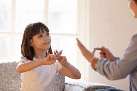 Photo pour Mom communicating with deaf daughter focus on kid sitting on couch in living room make fingers shape hands talking nonverbal. Hearing loss deaf disability person sign language learning school concept - image libre de droit