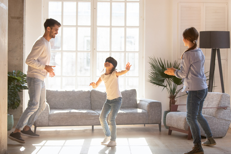 Photo for Blindfolded girl catching mother and father playing together hide and seek in living room, overjoyed funny parents having fun with preschool daughter. Weekend leisure activities, family games concept - Royalty Free Image