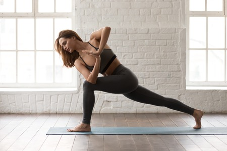Foto de Young attractive woman practicing yoga, beautiful girl in grey sportswear, pants and bra standing in Parsvakonasana pose, Side Angle exercise, working out at home or in yoga studio with white walls - Imagen libre de derechos