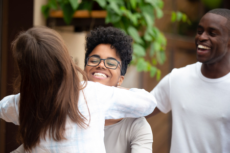 Photo for Smiling african american woman embracing girl friend saying hello at party, happy diverse female mates hugging laughing greeting each other attending reunion group meeting outdoors, multiracial friendship - Royalty Free Image