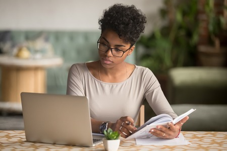 Photo pour Focused young african american businesswoman or student looking at laptop holding book learning, serious black woman working or studying with computer doing research or preparing for exam online - image libre de droit
