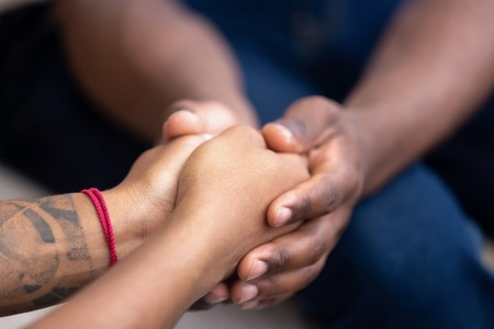 Foto de Black man friend holding hands of african woman, american family couple give psychological support, help trust care empathy hope in marriage relationships, comfort honesty concept, close up view - Imagen libre de derechos