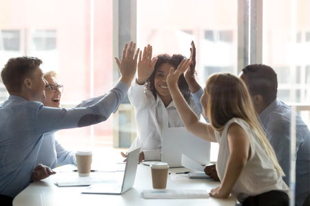 Foto de Happy multicultural executive team people give high five, diverse motivated office employees group engaged in teambuilding spirit promise trust integrity celebrate shared business success win concept - Imagen libre de derechos