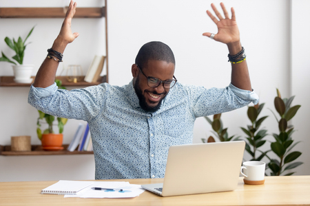 Foto de Euphoric overjoyed african black businessman happy to read great online news get promoted rewarded celebrating business success bet bid win, excited with good work results feeling motivated winner - Imagen libre de derechos