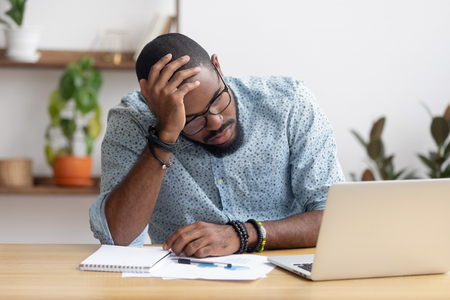 Photo pour Tired depressed bored african businessman frustrated by business failure bankruptcy looking at laptop feel exhausted having headache, upset stressed black office worker worried about problem at work - image libre de droit