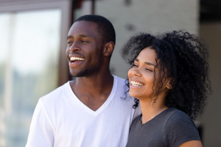 Foto de Smiling African American couple in love standing together outdoors, excited man and woman looking away, feeling happy about purchase new house, satisfied laughing customers, close up - Imagen libre de derechos