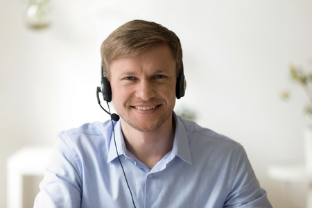 Foto de Head shot portrait of handsome smiling man wearing headset at office looking at camera. Call center introduction. Happy employee at workplace. People at work. Private entrepreneur. Video interview - Imagen libre de derechos
