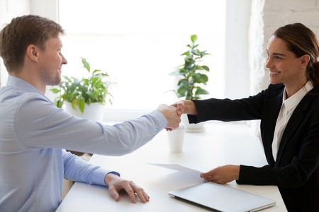 Photo for Welcome on board Confident young female employer and male candidate shaking hands and smiling sitting at workplace. Successful job interview. Got new job, good first impression, introduction - Royalty Free Image