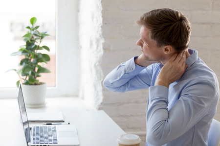 Foto de Millennial tired man having a neck pain. Male touching massaging neck sitting at workplace, suffering from discomfort long hours of sedentary life, overtime concept, muscles exhausted from overwork - Imagen libre de derechos