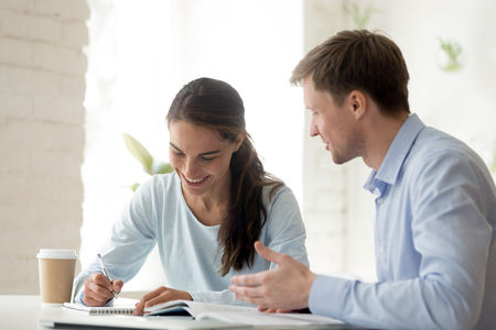 Photo pour Teacher and student having fun learning. Happy school girl writes notes in notebook. Smiling professor explains subject to young student. Girl taking extra classes. Coworkers at work in office - image libre de droit