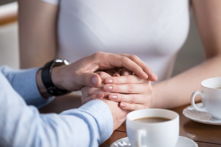 Foto per Close up of male and female hands. Millennial couple gently holding each other with hands. Young pair having romantic breakfast. Helping, taking care, trust in marriage, love and support concept - Immagine Royalty Free