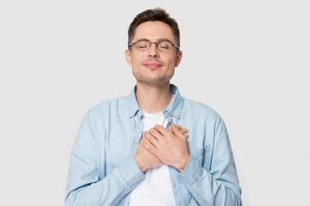 Photo pour Calm young Caucasian male in glasses isolated on grey studio background hold hands on chest close to heart feel grateful, thankful European man in appreciation thanking fate. Gratitude concept - image libre de droit