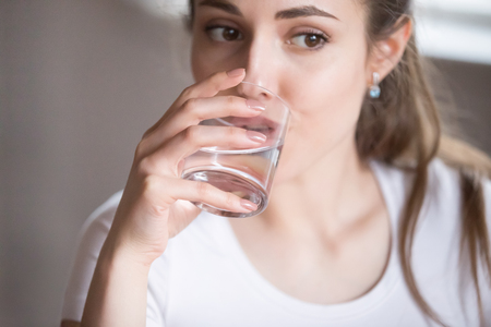 Photo pour Close up top view woman drinking clear water from glass. Millennial beautiful female taking pill, tablet, medication, refilling water balance. Thirsty, dehydration, healthcare, medical concept - image libre de droit