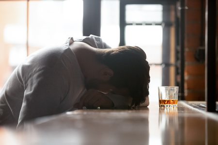 Photo pour Drunk boozy man sleeping lying on bar counter after drinking large amount of alcoholic beverage glass of whiskey strong booze near him, concept of alcohol use disorder AUD alcoholism health problems - image libre de droit