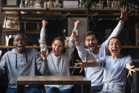 Foto de Multi-ethnic people looking at camera sitting at cafe public place screaming shouting feels overjoyed happy by favourite football club team winning get victory, sports betting, lottery winners concept - Imagen libre de derechos