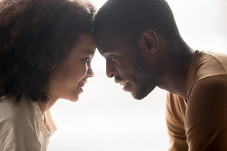 Photo pour Close up profile african father and cute daughter faces touch foreheads looking in eyes each other feels love understanding, enjoy tender moment, bonding connection care and warm relationships concept - image libre de droit